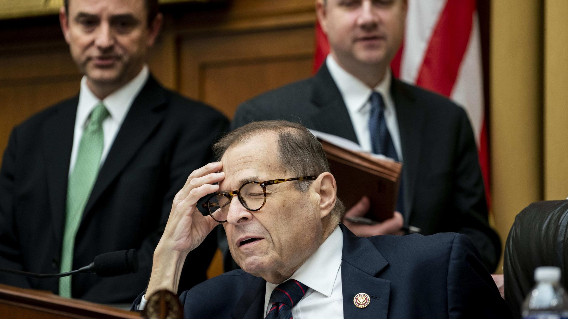 In this image, Nadler shuts his eyes and holds his head while sitting down. Two men stand behind him, on either side of him.
