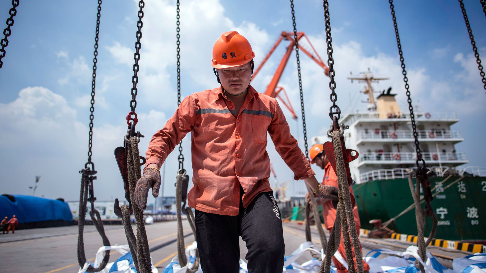 Chinese worker unloading bags of chemicals at a port