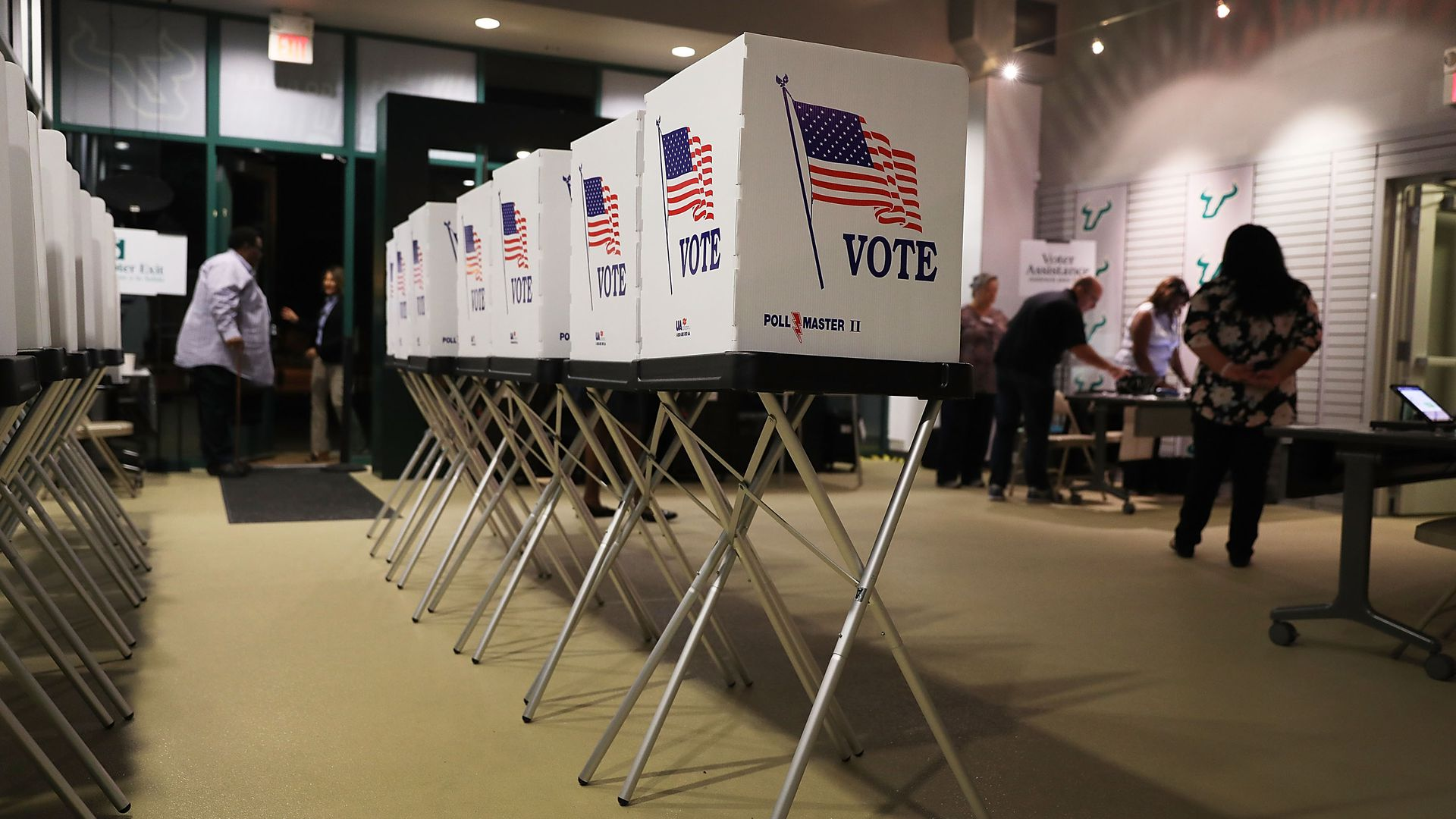 In this image, a row of voting booths are seen in a room with darkened windows.