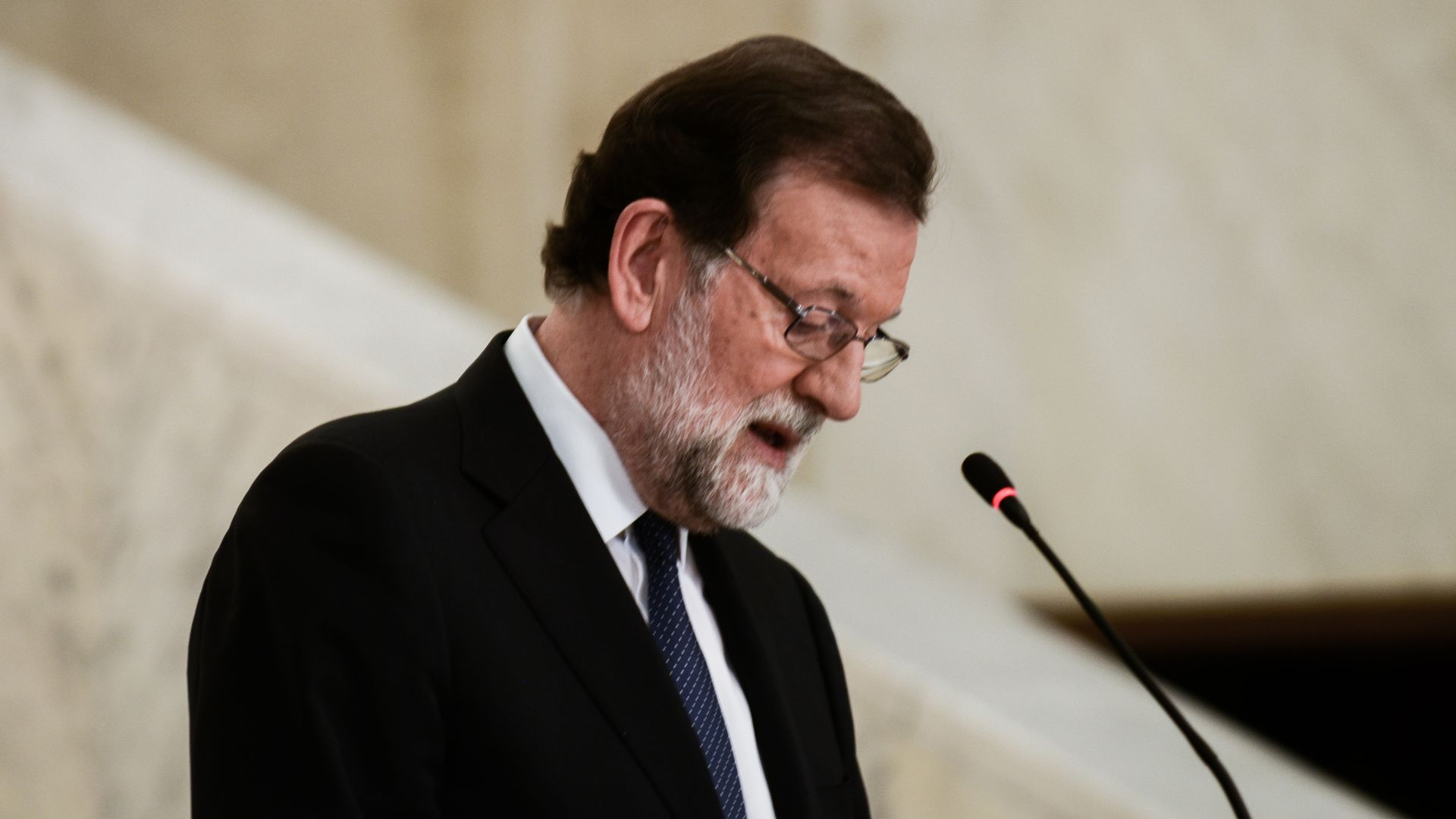 Spanish PM Mariano Rajoy looks down while speaking at a press conference