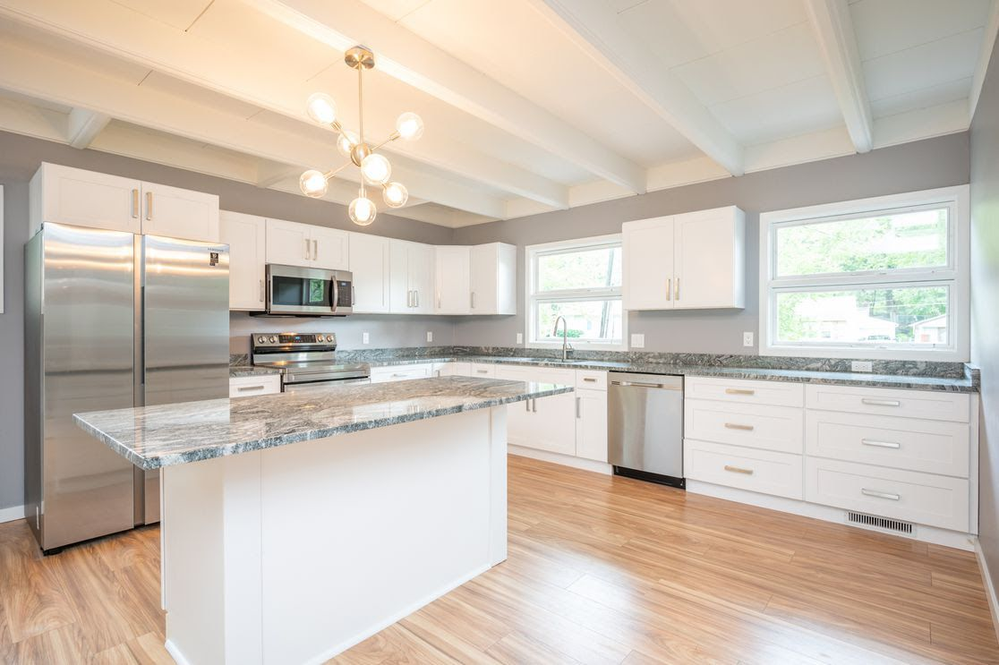 A kitchen with marble countertops and white furnishings in a Des Moines home for sale.