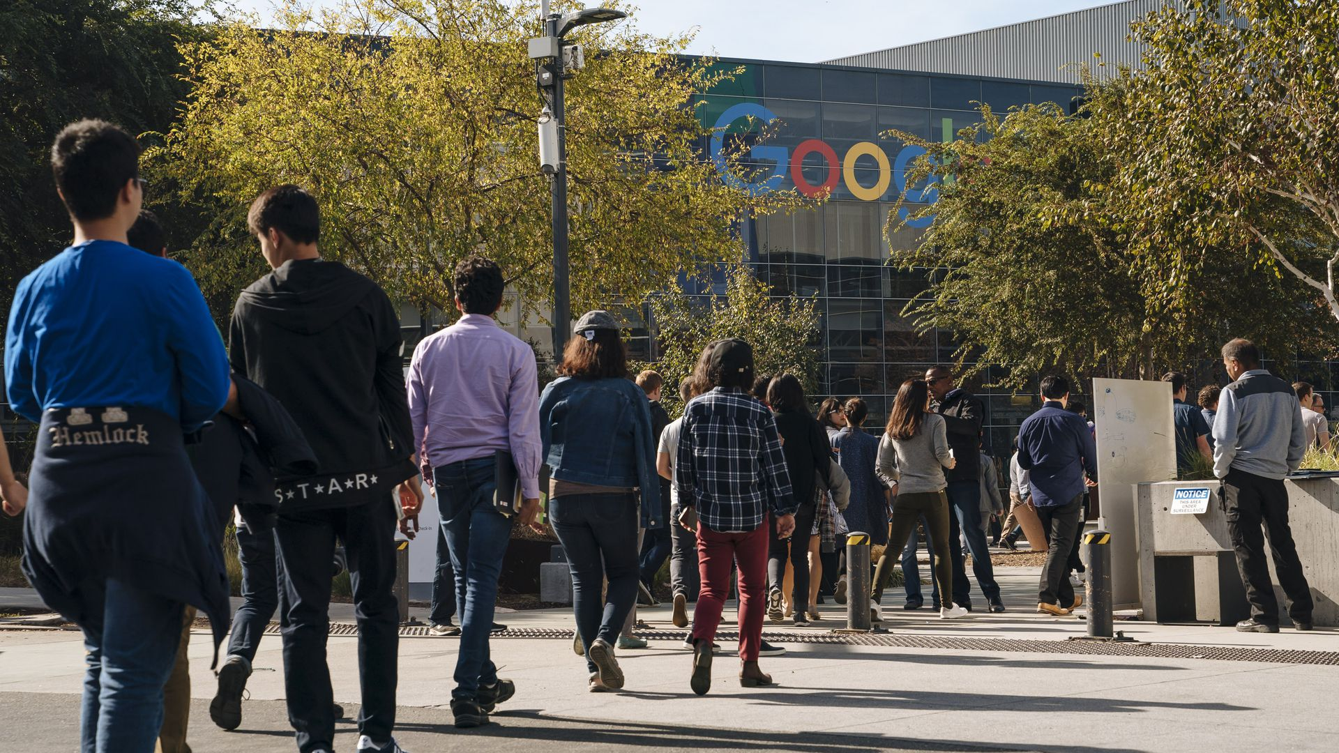 Google employees walkout in diagonal line with Google logo in background.
