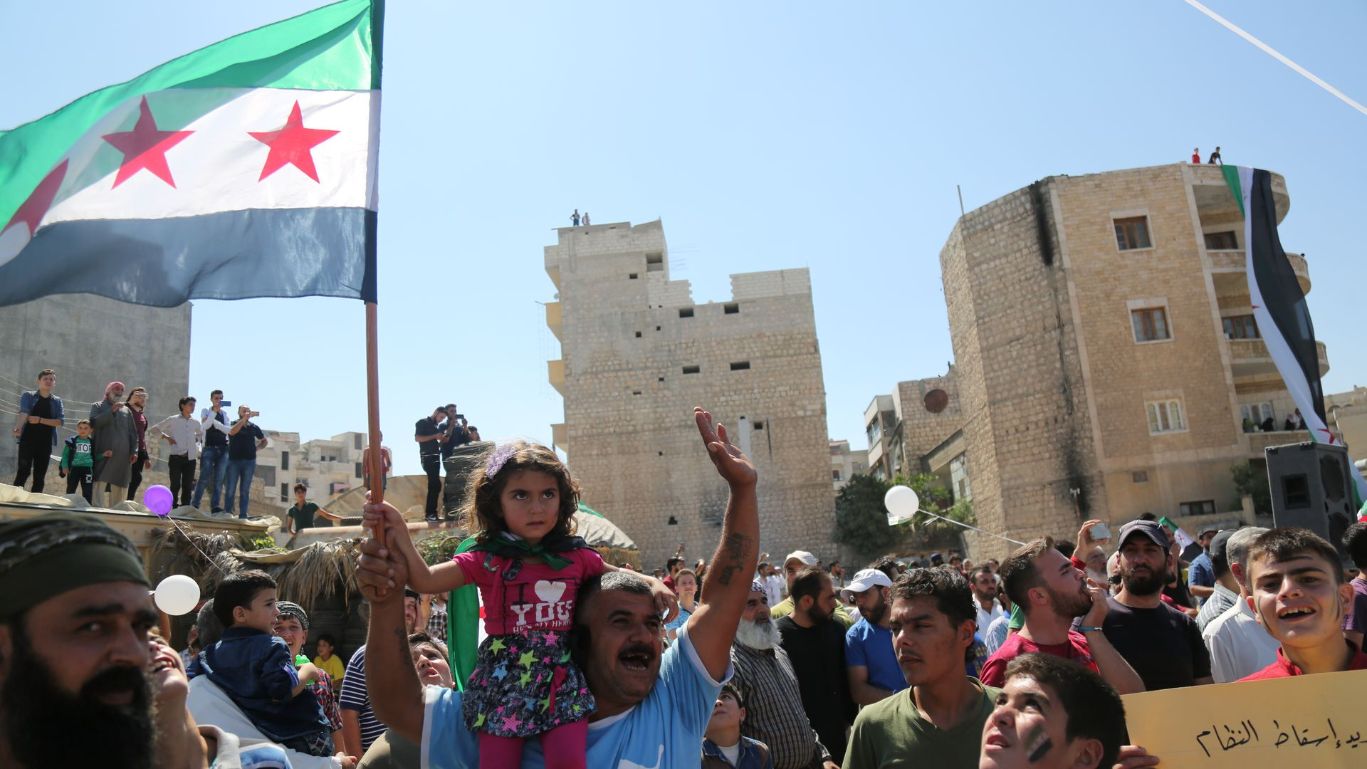 People of Idlib hold a Syrian revolution flag during a demonstration to demand the international community stop the military campaign by Syrian regime