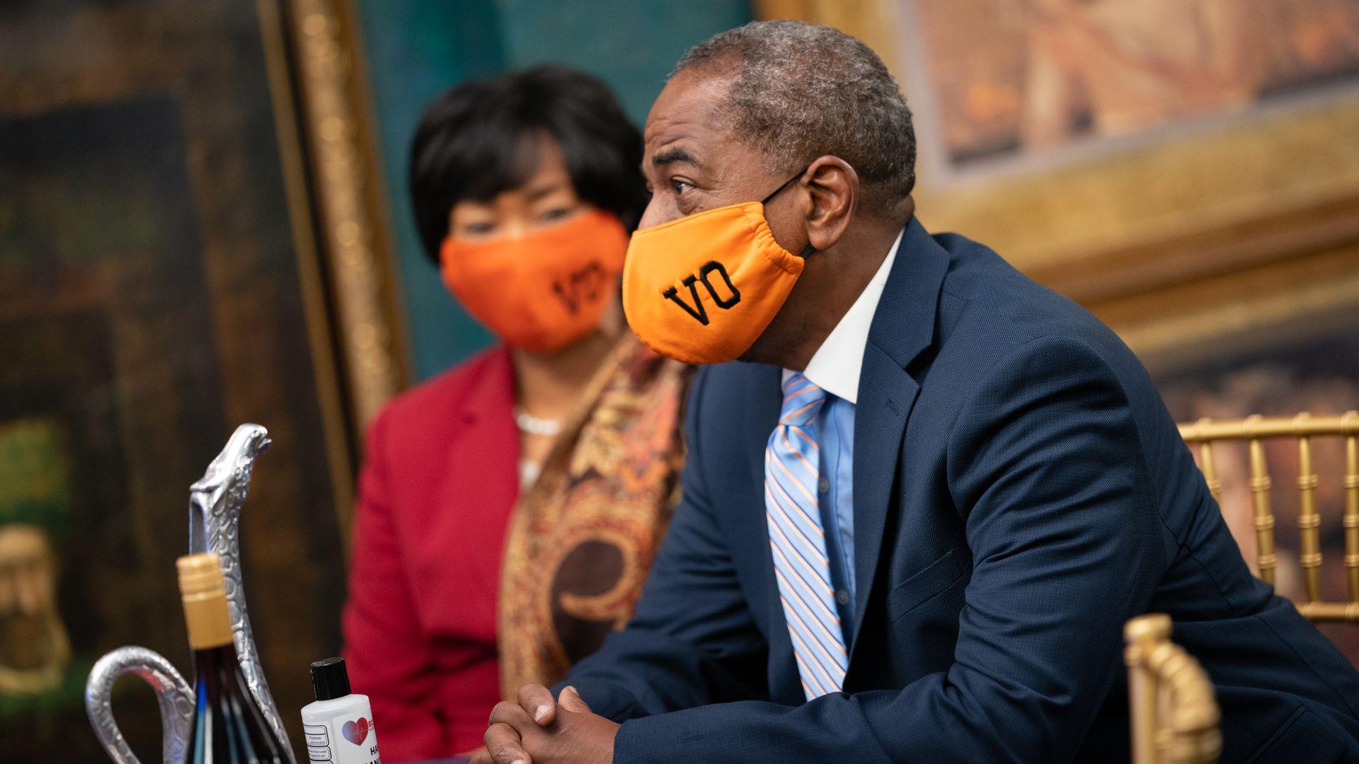 "Vincent Orange shown wearing an orange mask bearing his initials ""VO."""