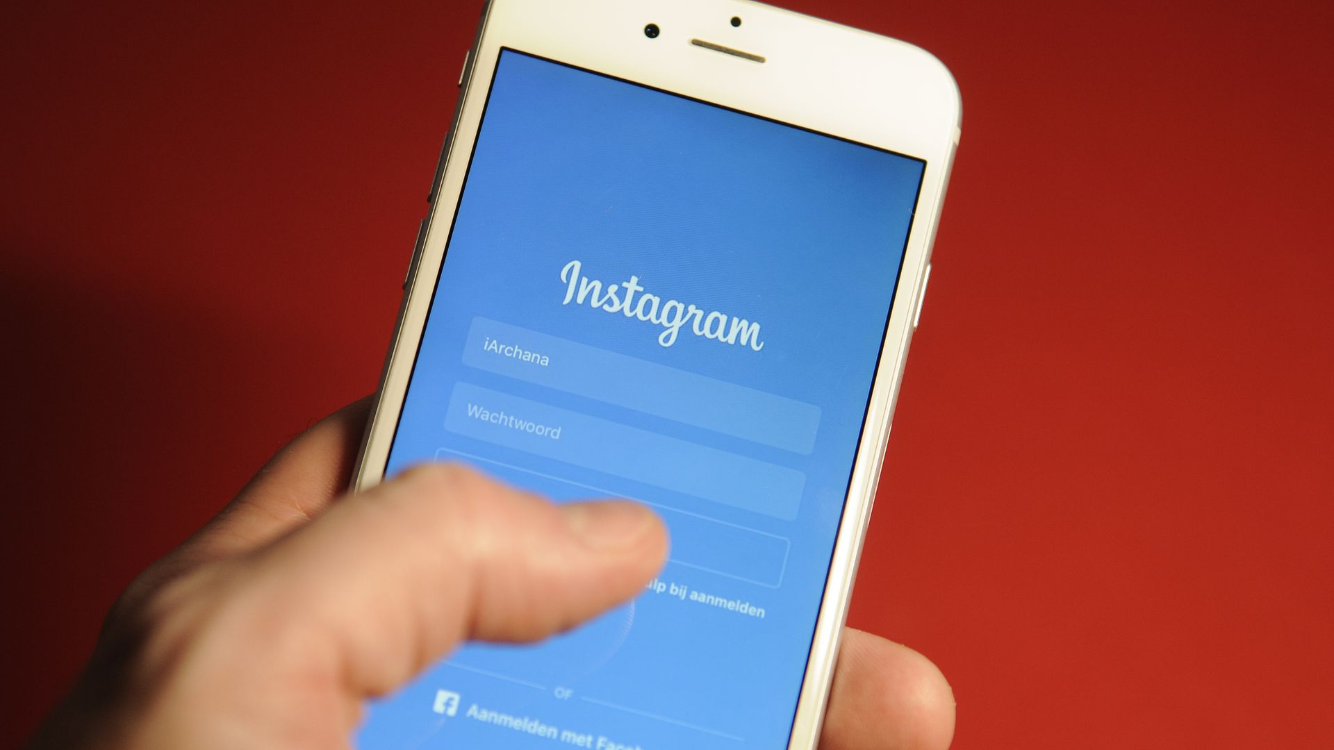 Hand holds phone on Instagram login page over red background