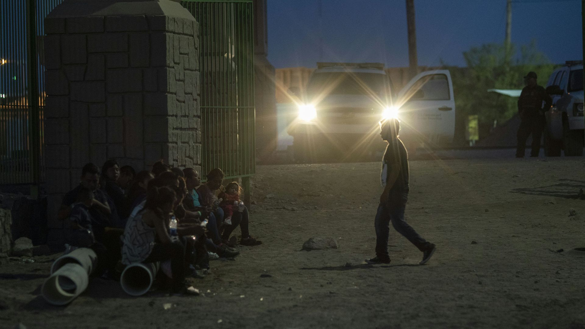 Migrants waiting in the dark near the border to be taken to a border patrol processing center.