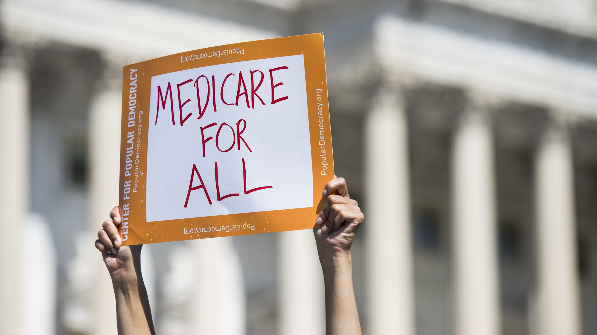 person holds up medicare for all sign