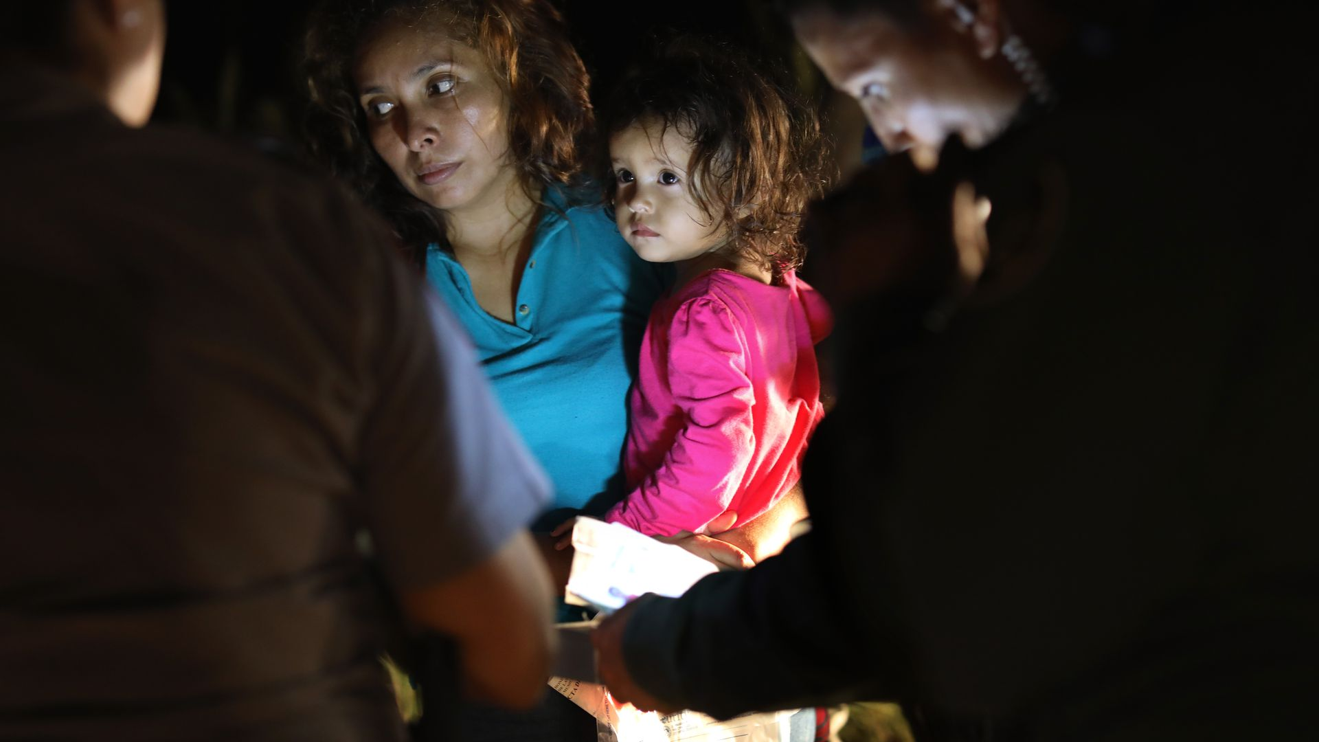 An immigrant holds her daughter while having paperwork looked at by immigration law enforcement officials