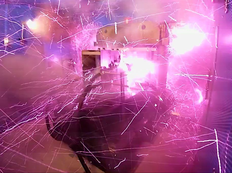 Purple sparks fly from a large mechanical device inside a small room.