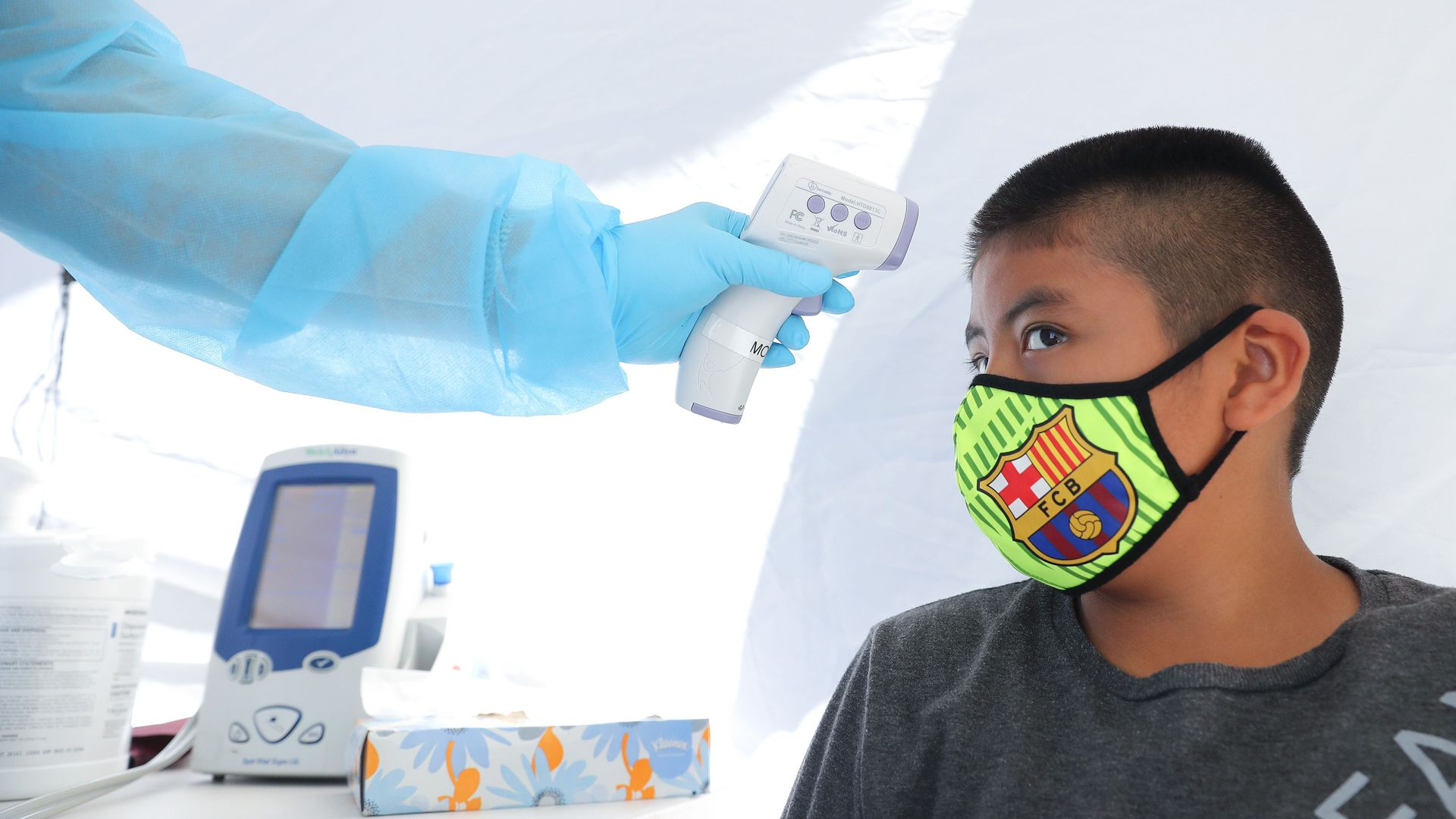 A boy has his temperature checked as he receives a free COVID-19 test in Los Angeles