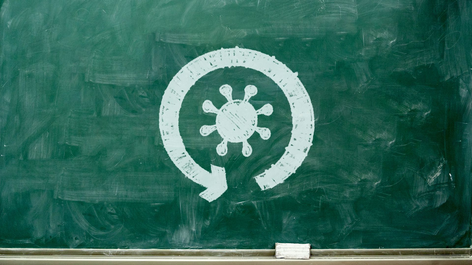 Illustration of a chalkboard with a circular arrow and a coronavirus icon drawn in chalk.