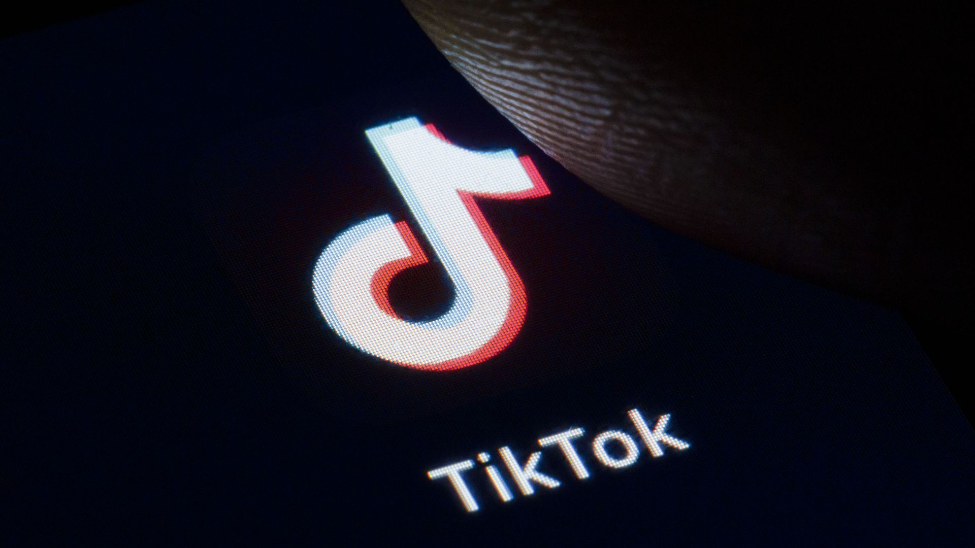 In this image, a thumb hovers over the TikTok logo displayed on a smartphone screen.