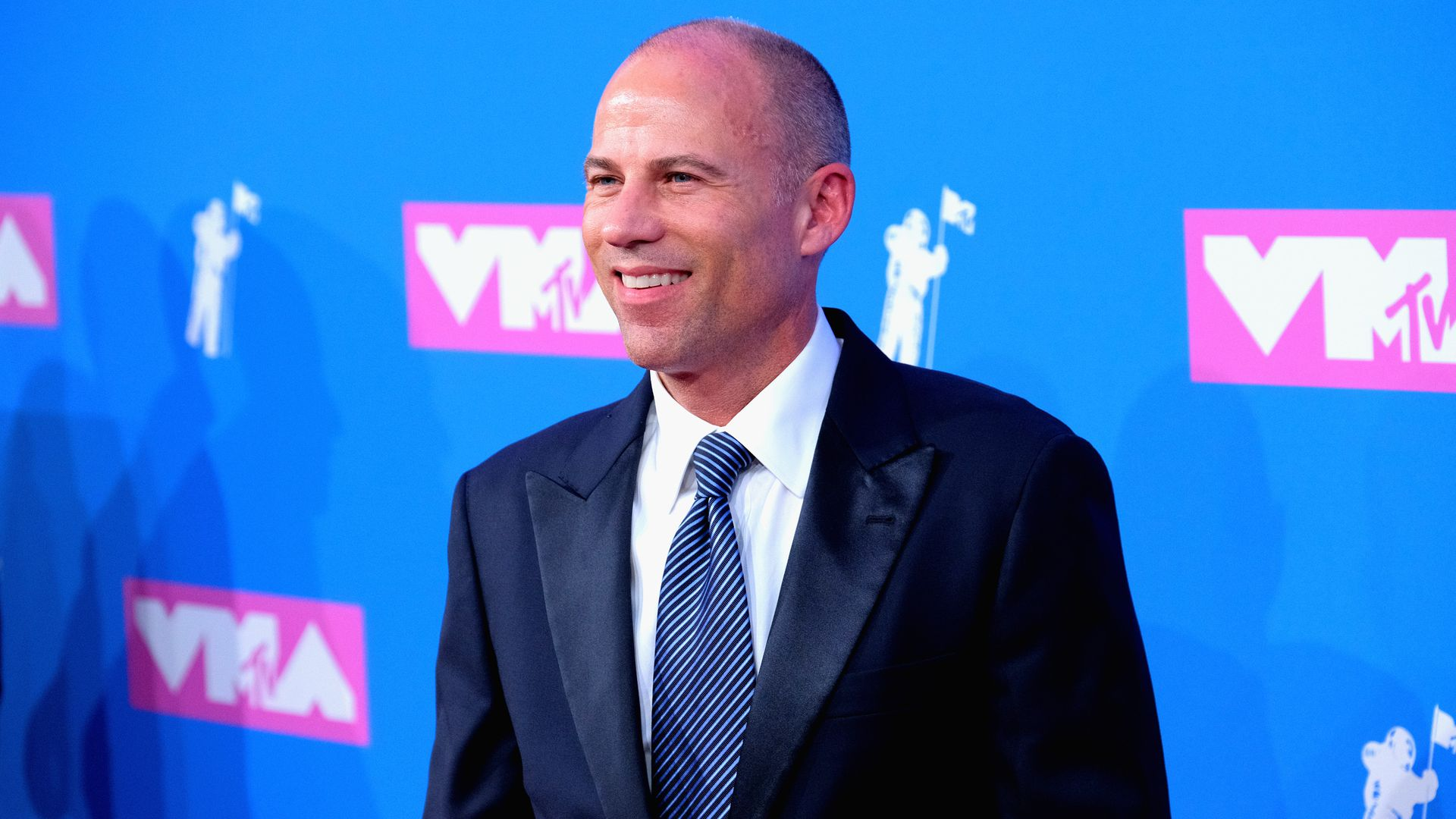Michael Avenatti smiles on the pink carpet at the VMA's step and repeat