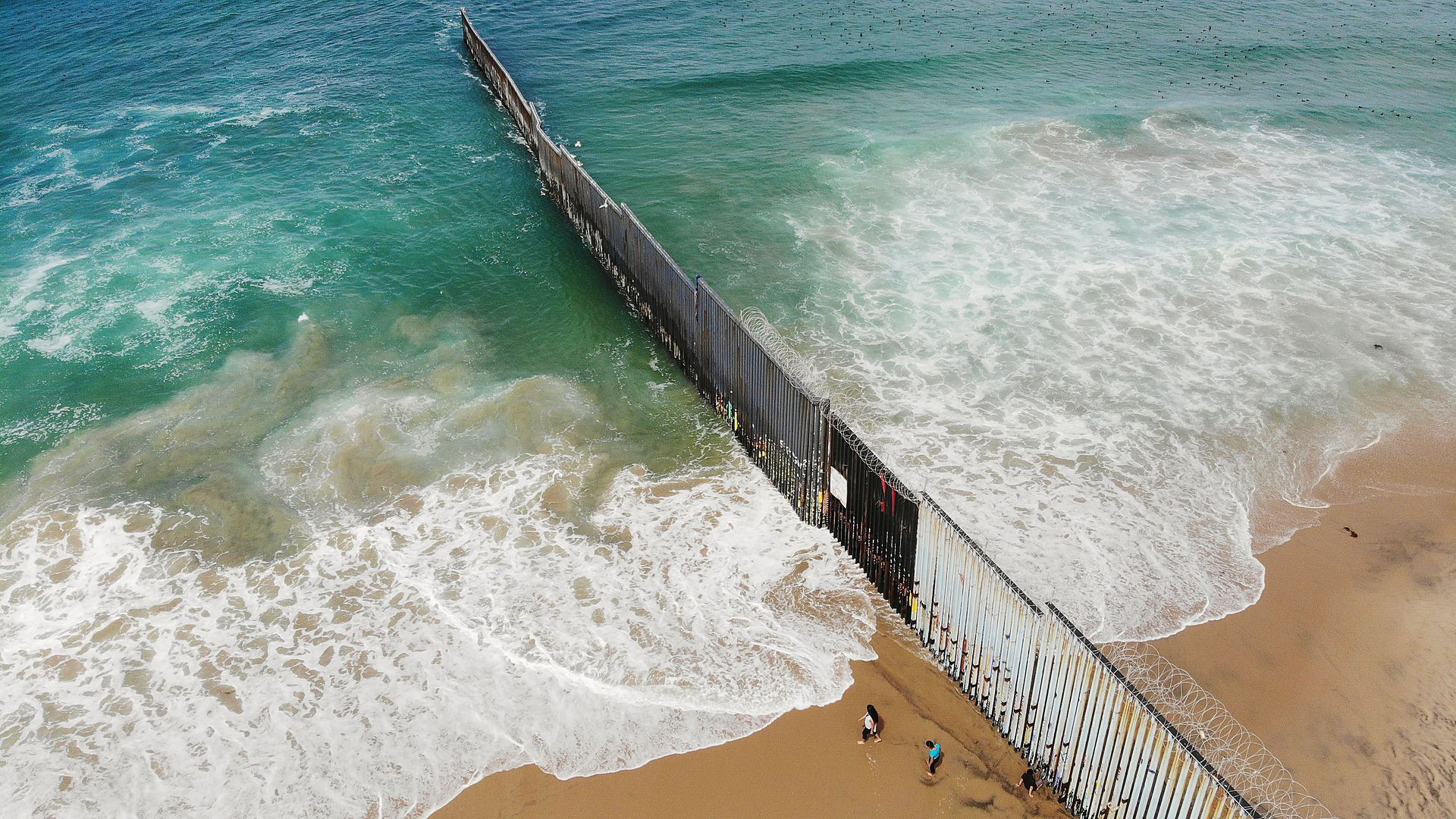 In this image, three people from Mexico walk along a tall fence the southern border that leads down the beach and into the ocean.