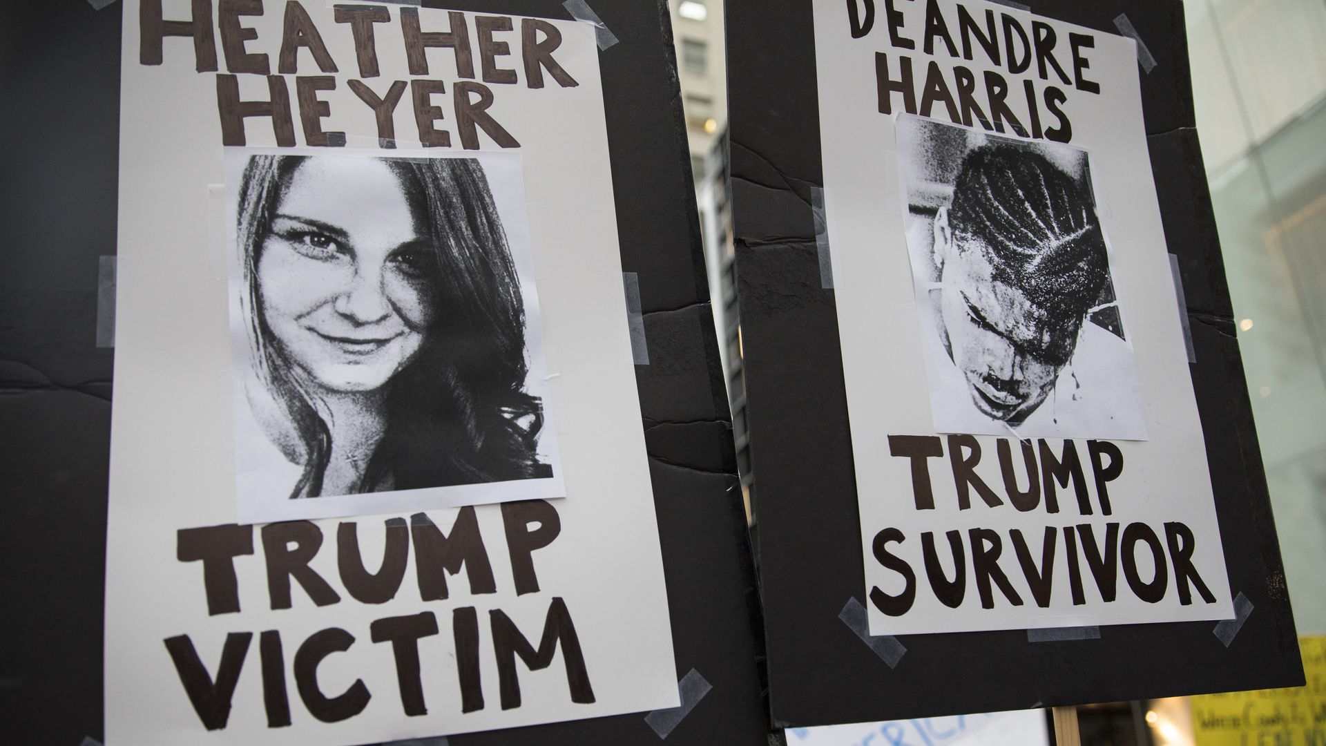 protest signs with images of Heather Heyer and Deandre Harris
