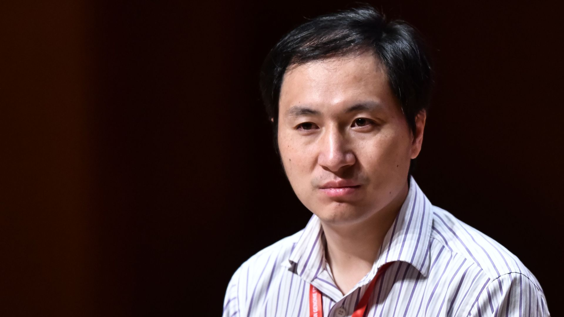 In this image, Chinese scientist He Jiankui sits and listens to someone speaking