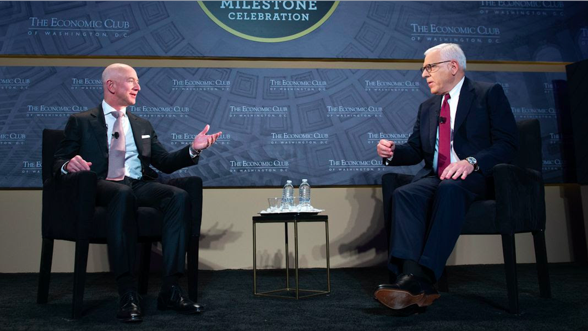 Bezos motions with his arms while talking to Rubenstein onstage