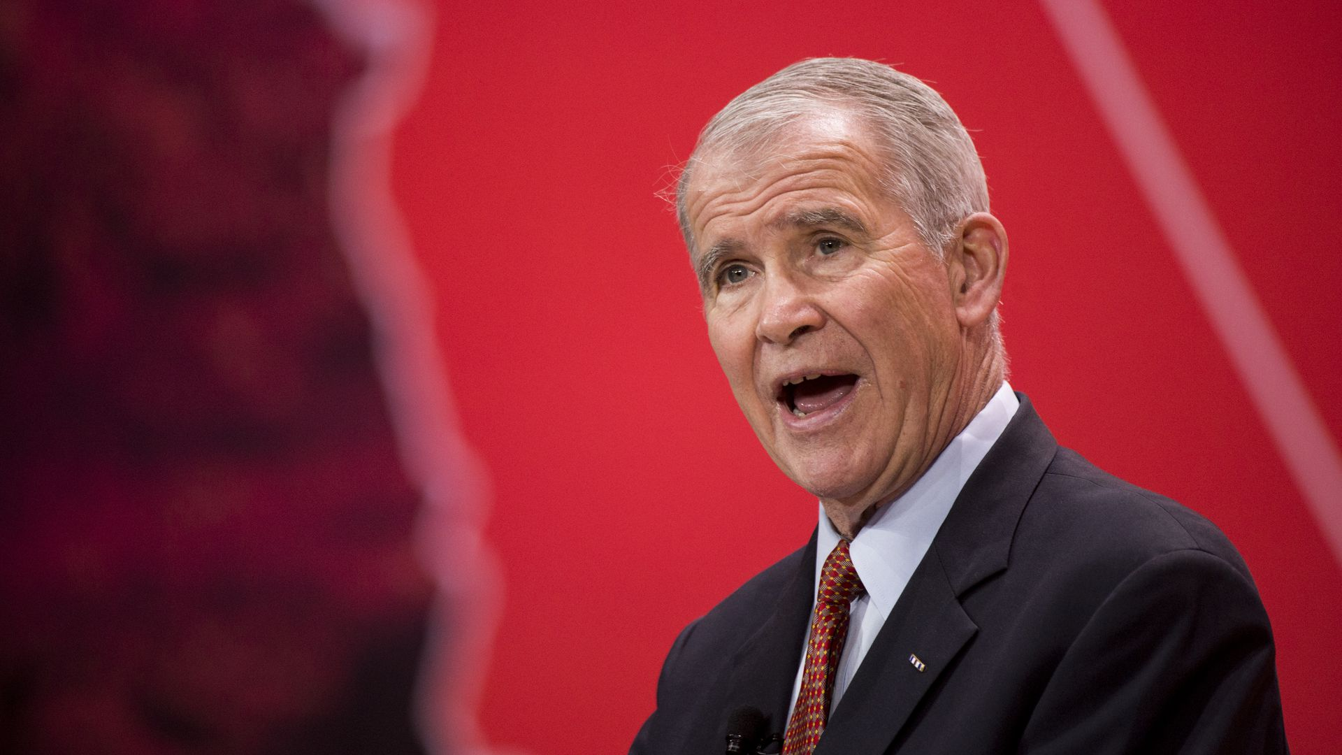 Oliver North speaking before a red background.