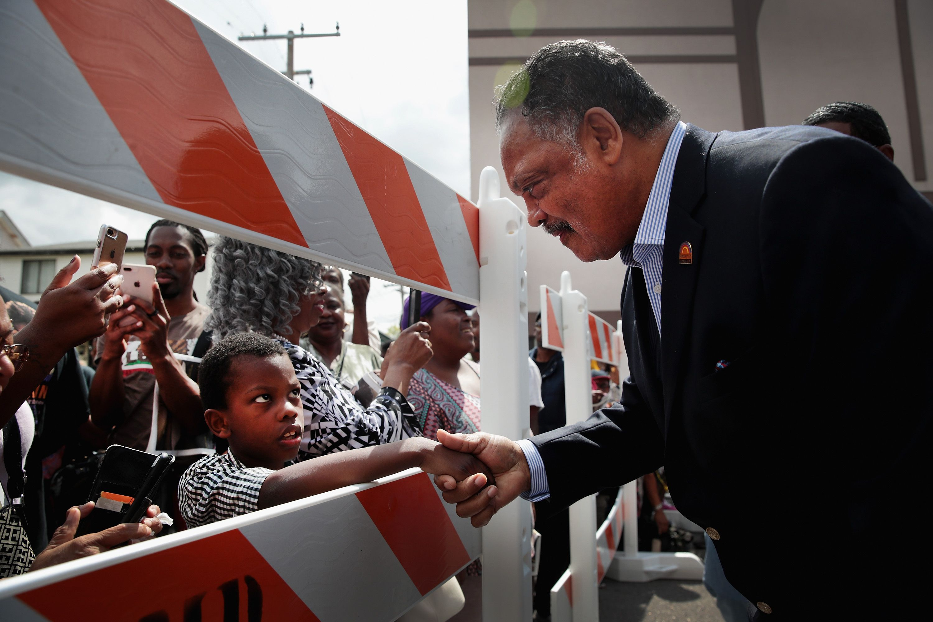Rev. Jesse Jackson shakes the hand of a young boy.