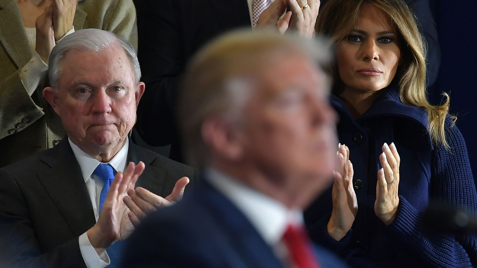 Jeff Sessions claps behind Donald Trump's blurry profile at a speech