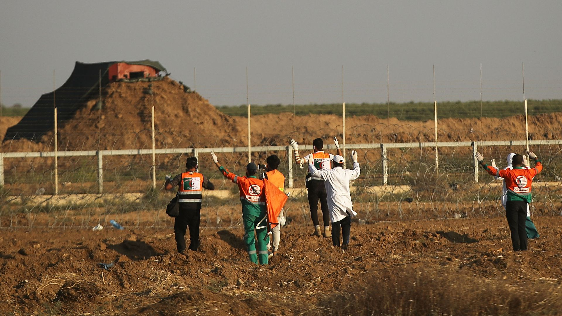 medical workers approach Israeli-Gaza border fence with arms up