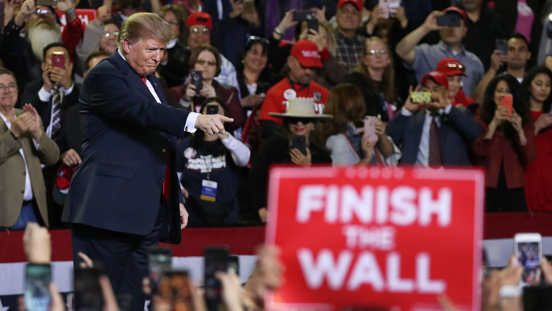 "President Trump at a rally as a supporter holds a sign reading ""Finish the Wall"""