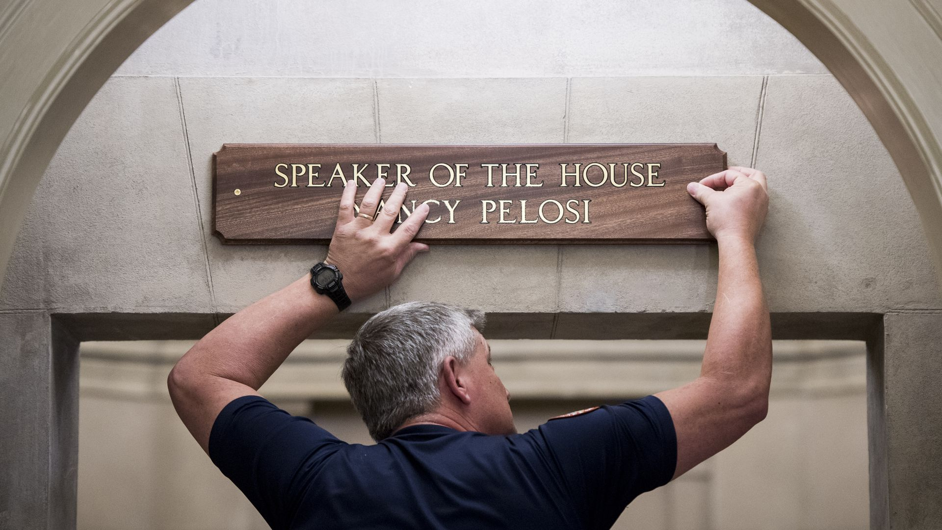 Worker puts up Nancy Pelosi Speaker of the House plaque.