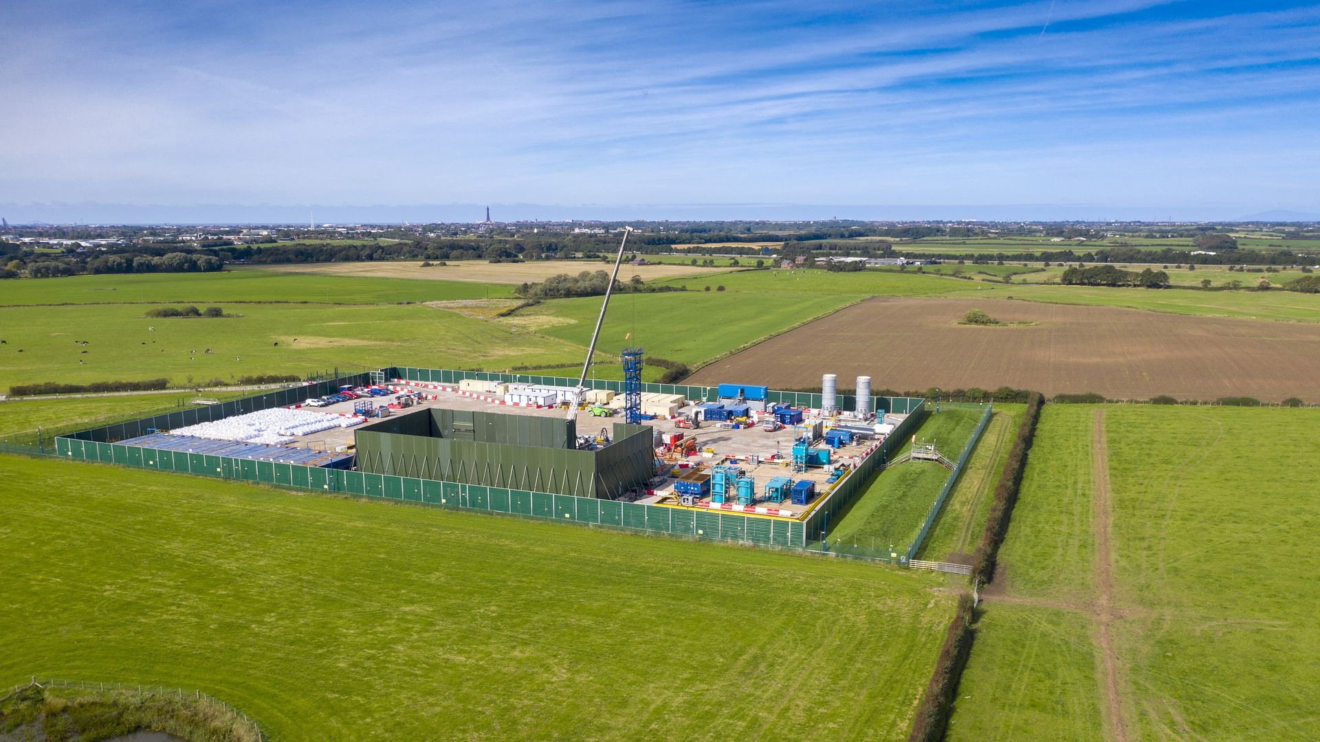 The photo shows a hydraulic fracking site in England, surrounded by verdant grass.