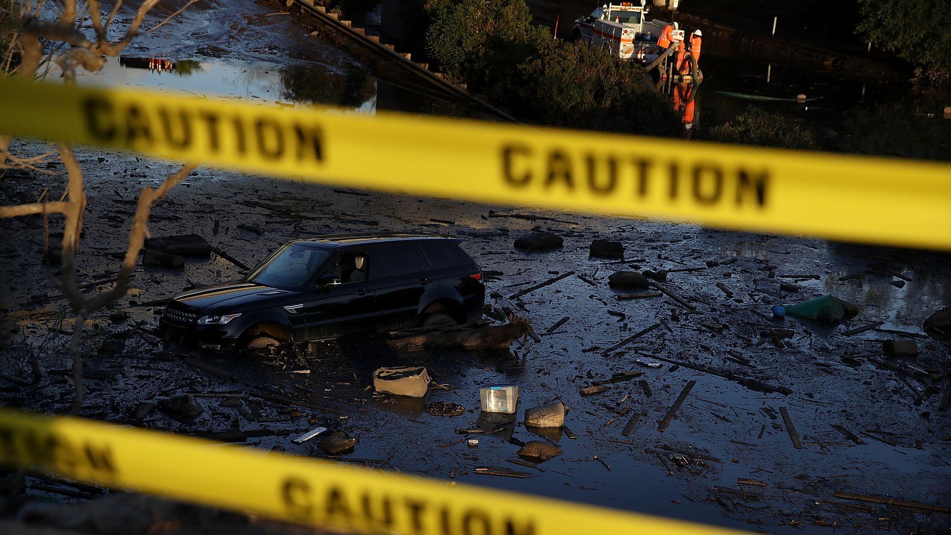A car sits in mud and debris on Highway 101