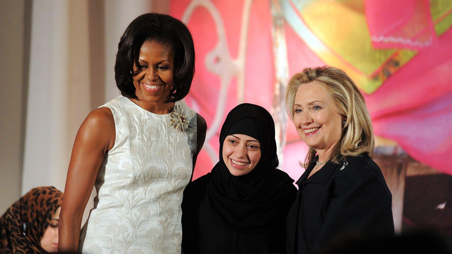 Saudi human rights activist Samar Badawi accepting an award next to Michelle Obama and Hillary Clinton