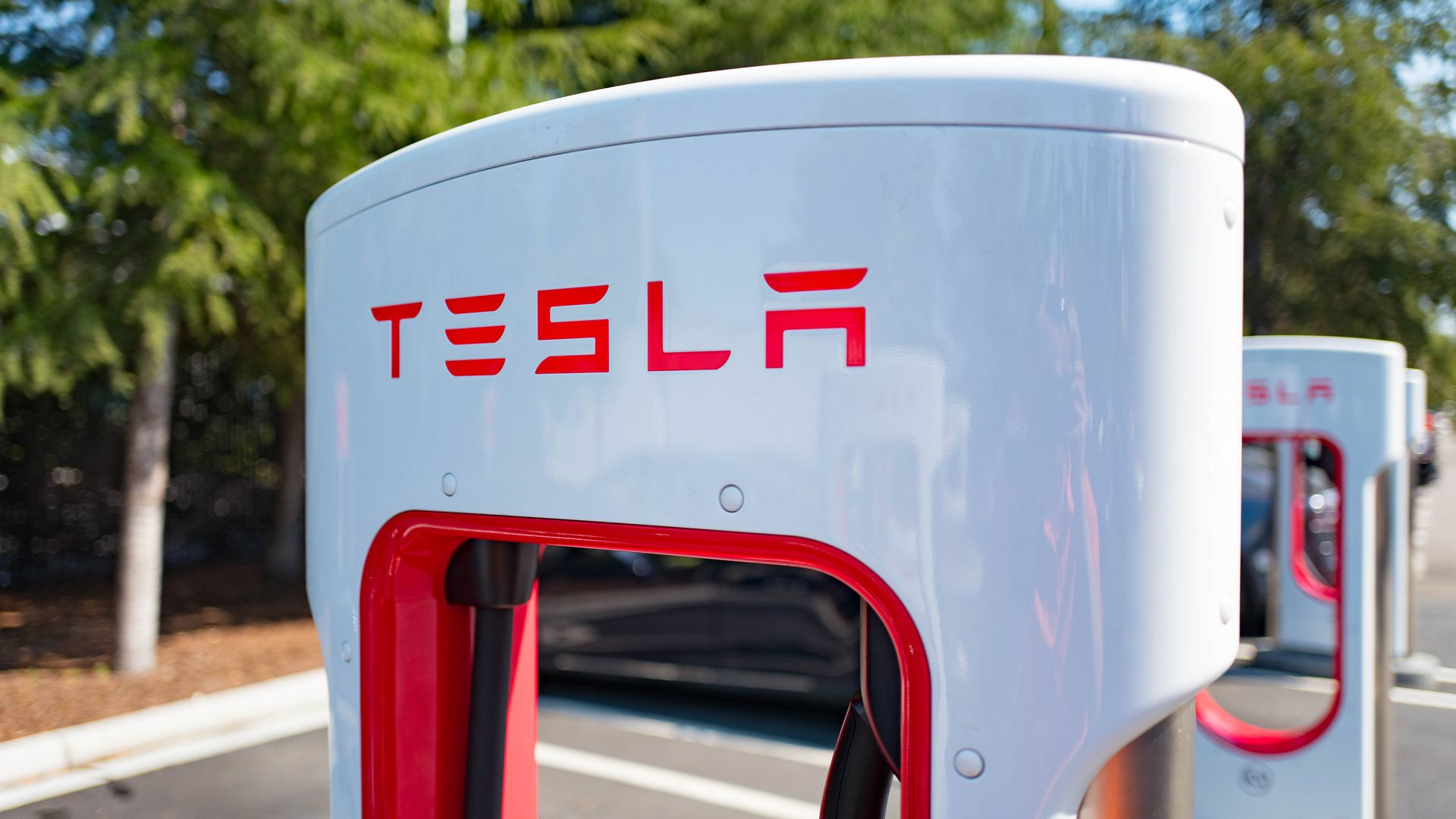 This image shows a Tesla supercharger in a parking lot.