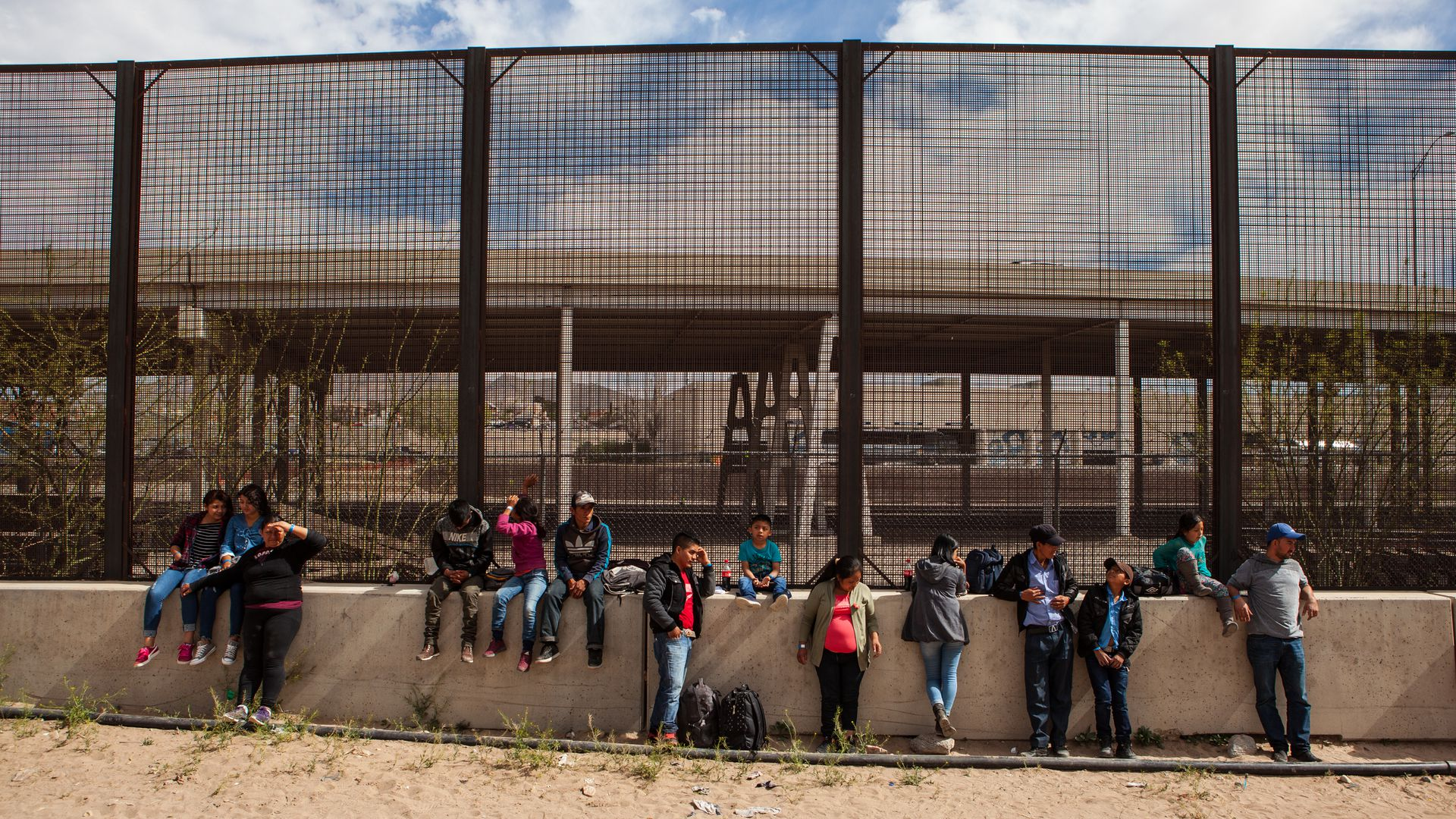 Central American migrants standing in front of a U.S.–Mexico border wall