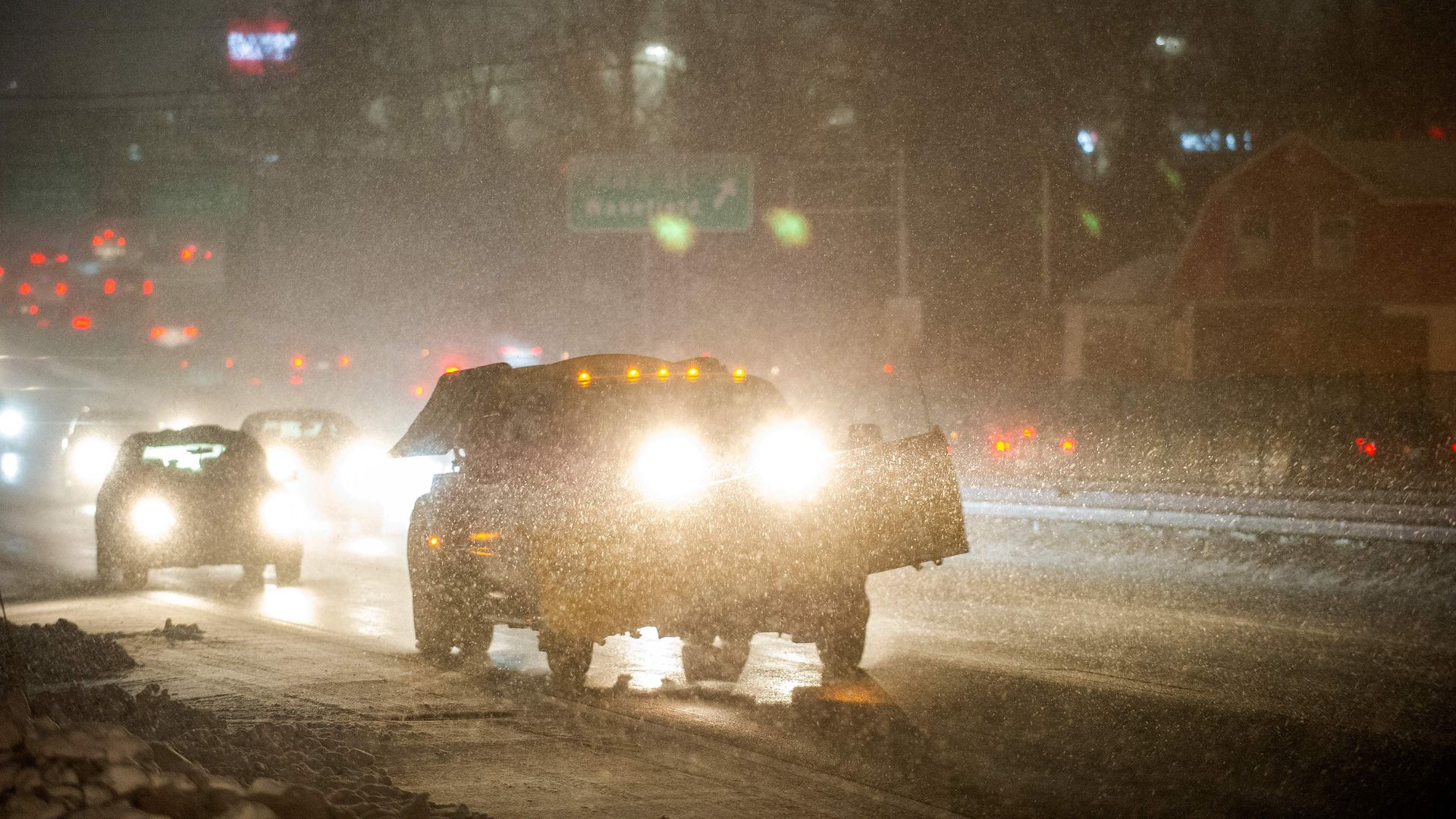 A plow makes it way down US Route 1, throwing sand, as cars are engulfed by snow in the early stages of the second part of Winter Storm Ezekiel in Saugus, Massachusetts on December 2
