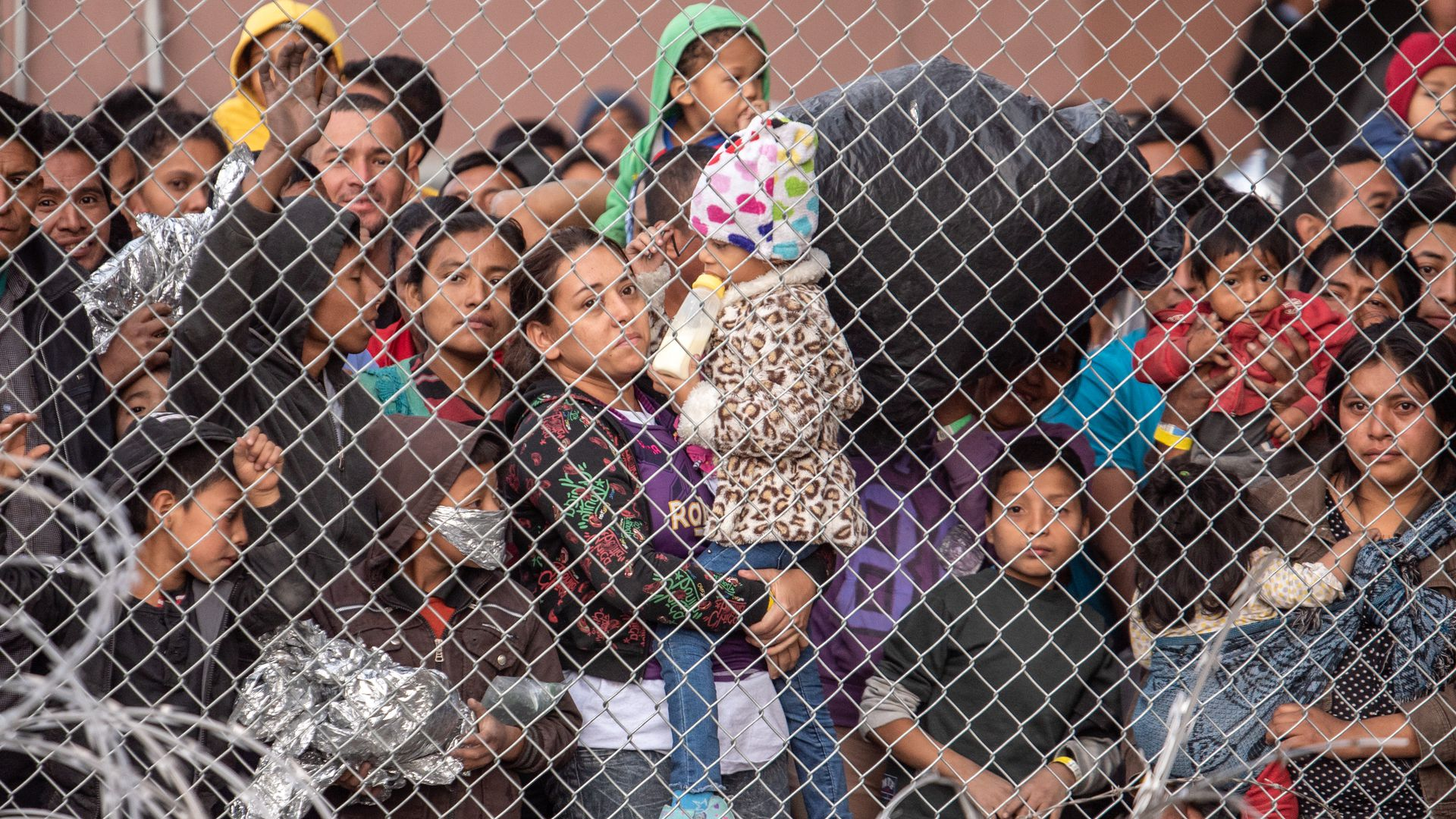 Migrants are gathered inside the fence of a makeshift detention center in El Paso, Texas.