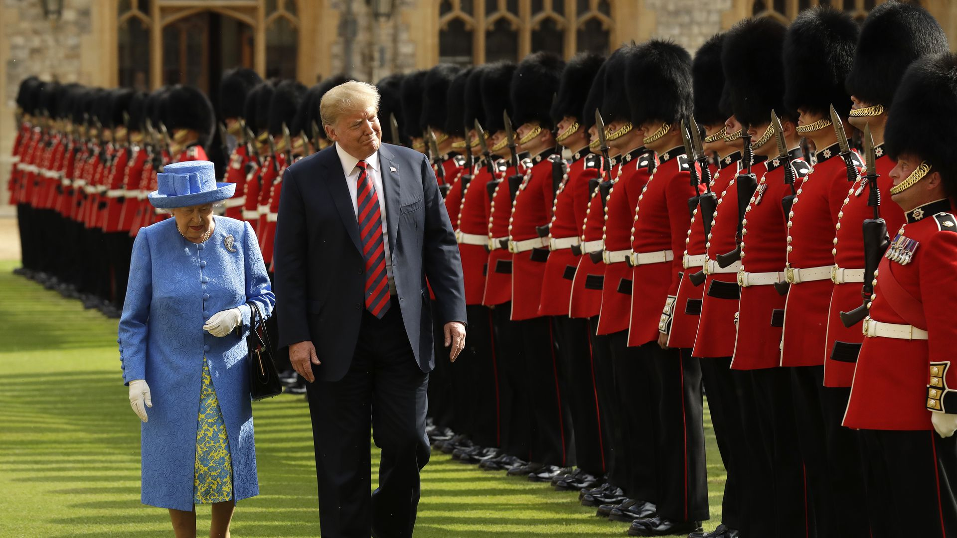 Trump, next to the Queen, walks past a line of guards in British uniform