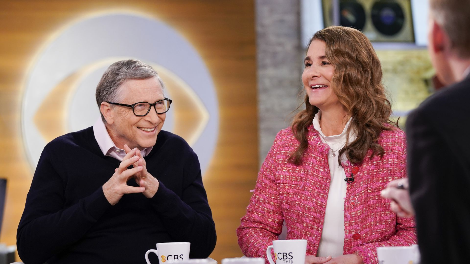 Bill Gates and Melinda Gates laugh on the set of CBS this morning, with the CBS symbol in the background.