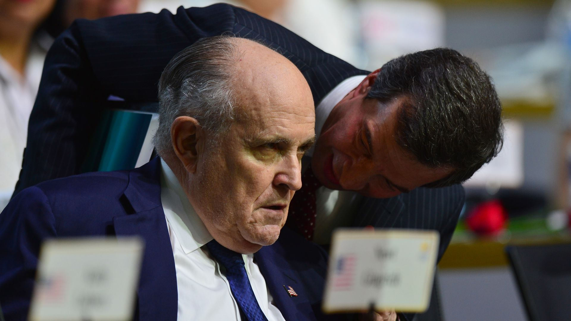 An aide whispering in Rudy Giuliani's ear