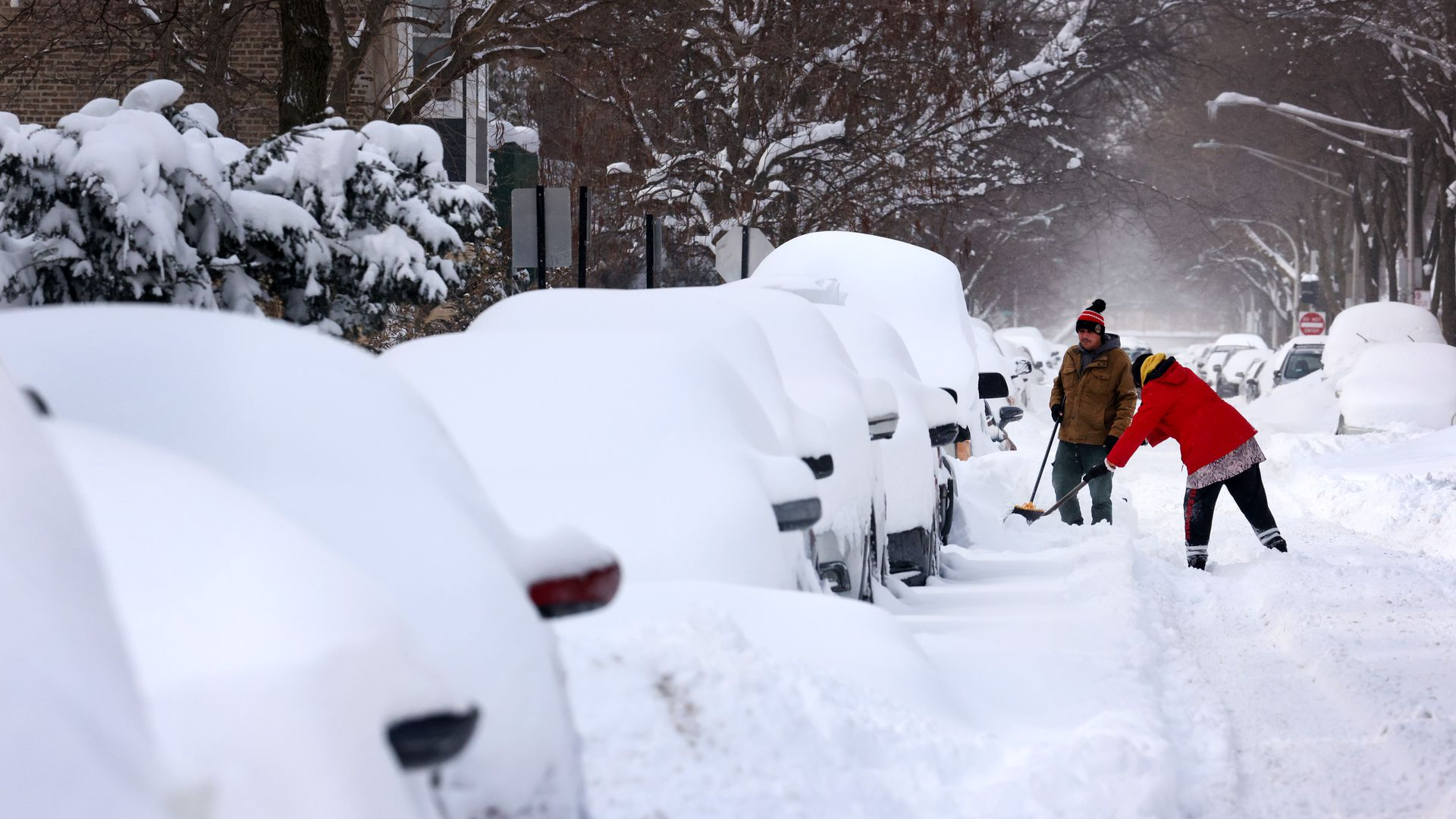 Photo of two people shoveling snow next to a line of cars
