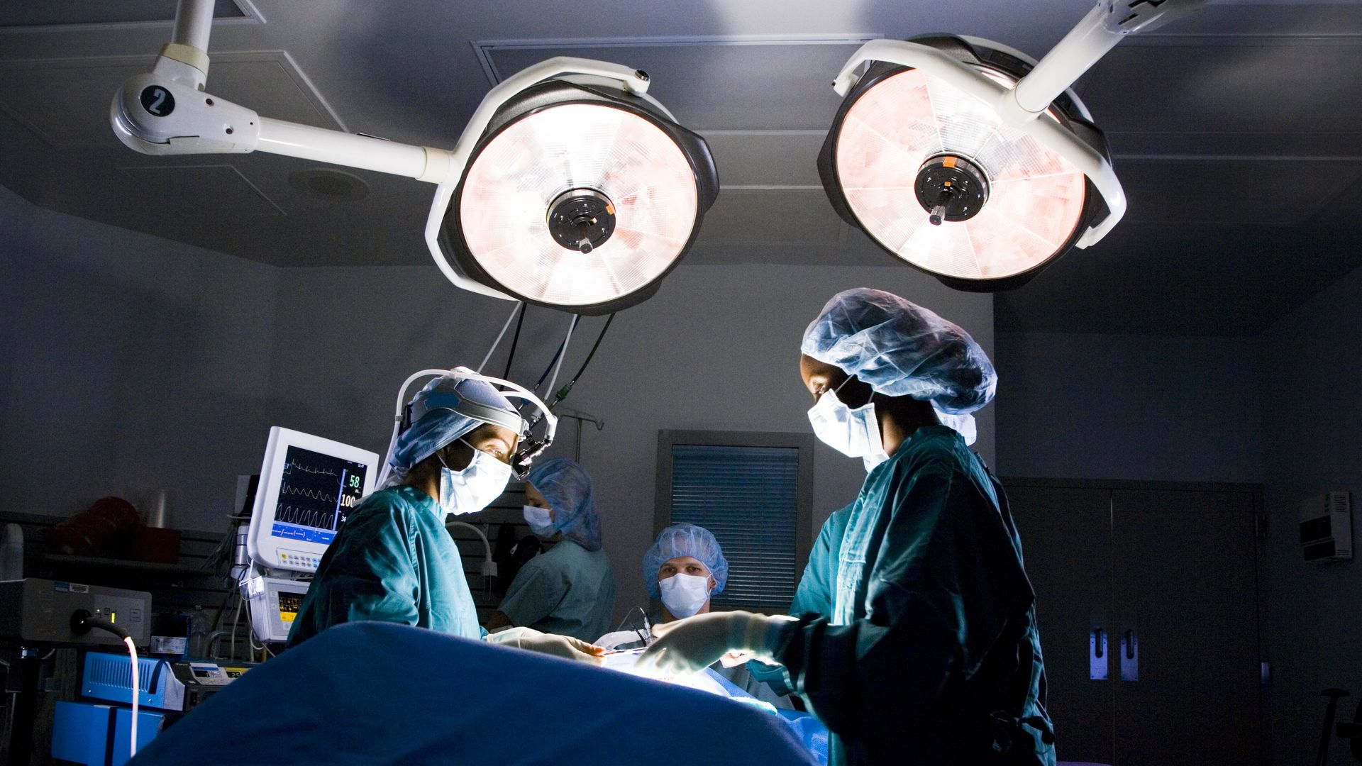 In this image, three surgeons stand under bright lights in a dark operating room.