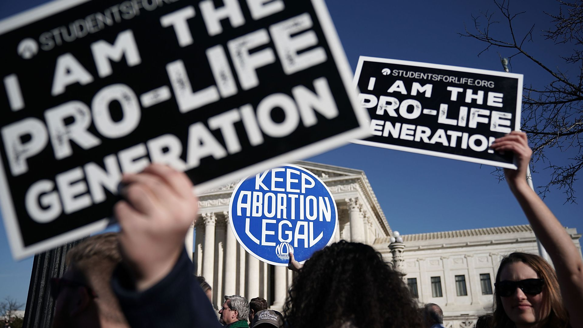 Pro-life activists hold up signs in front of a pro-choice activist.