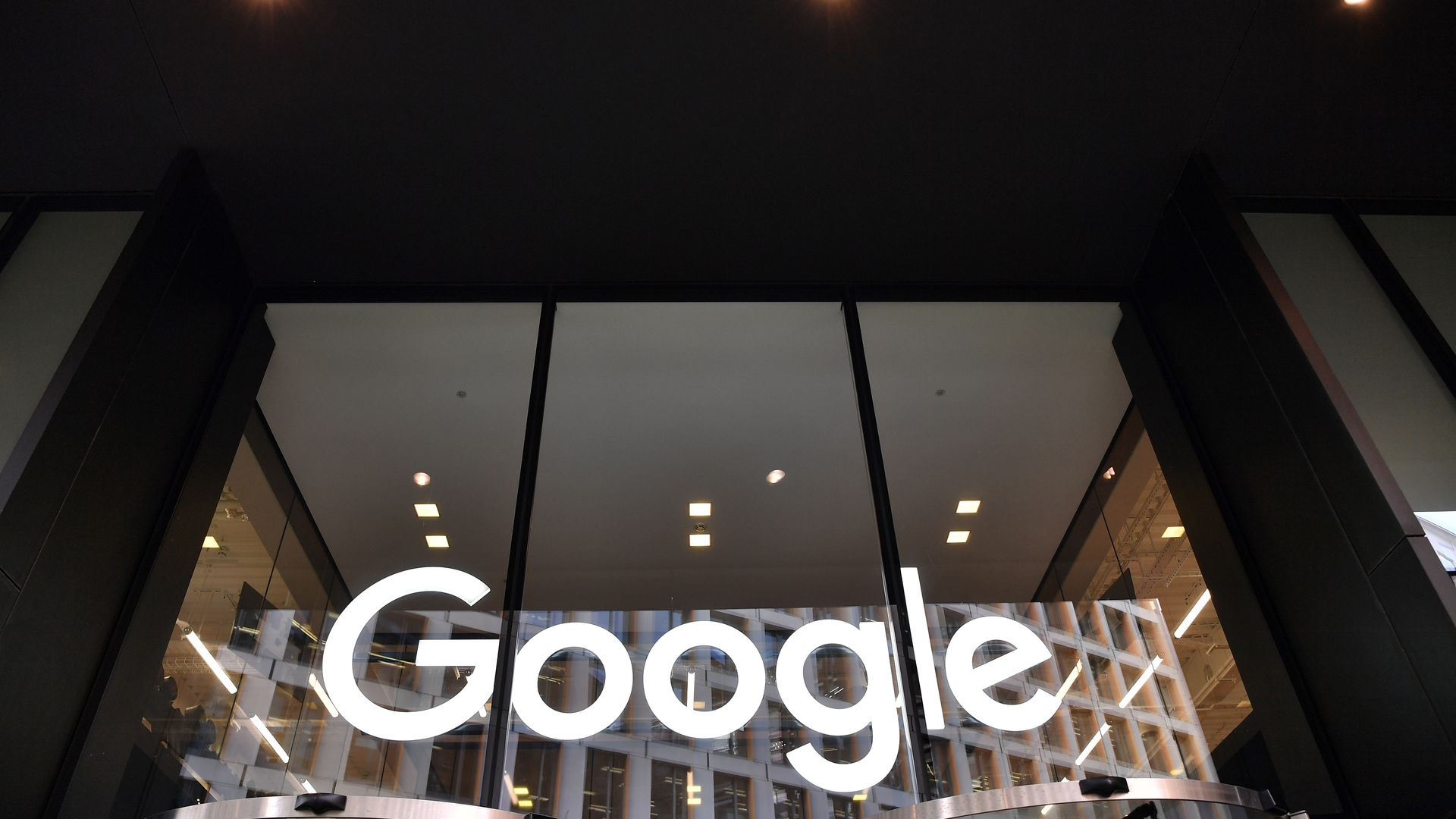 In this image, the white Google logo is seen at the bottom of three large glass windows on the side of a building.