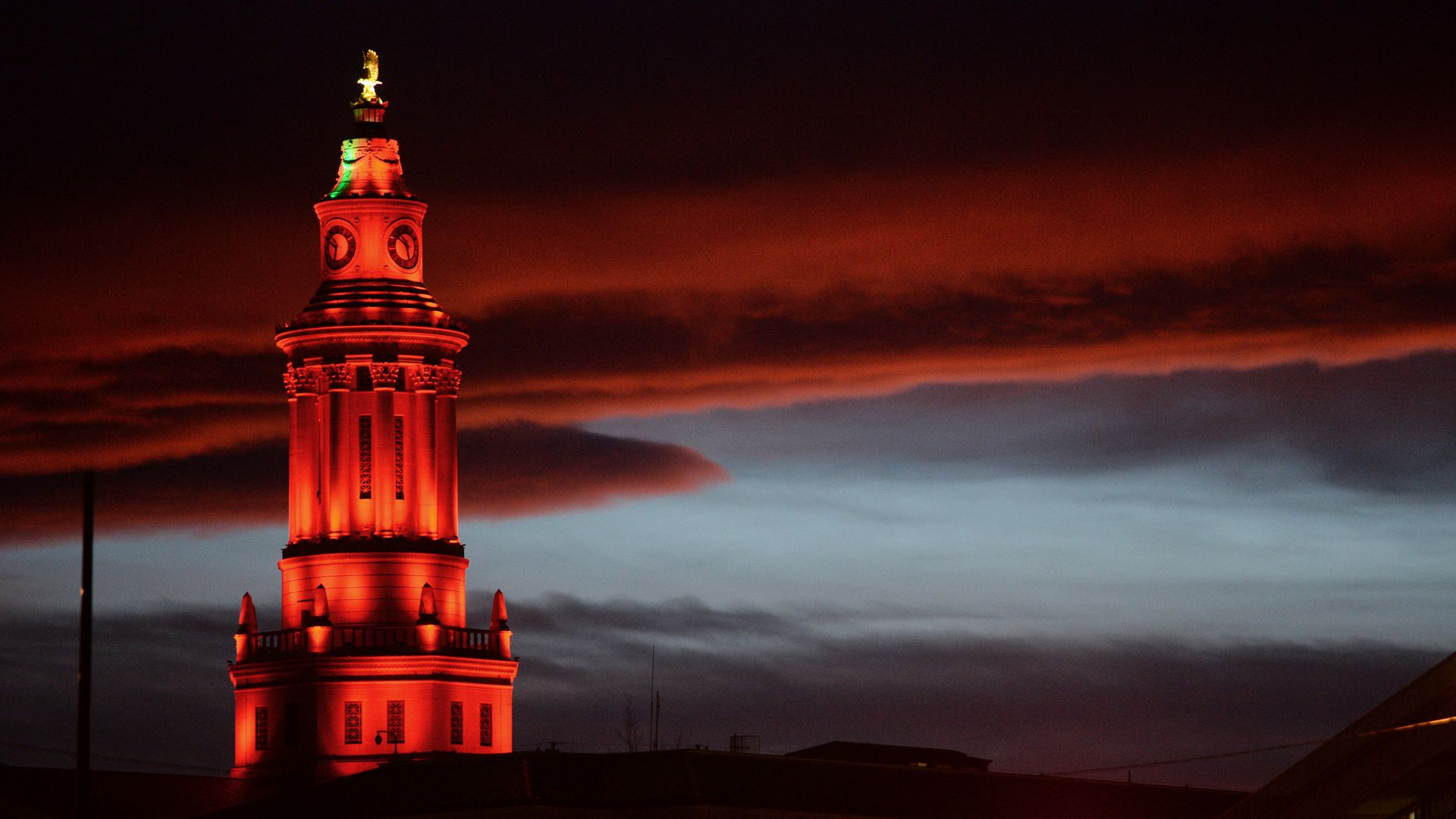A photo of the top of the Denver City Hall building lit up in red