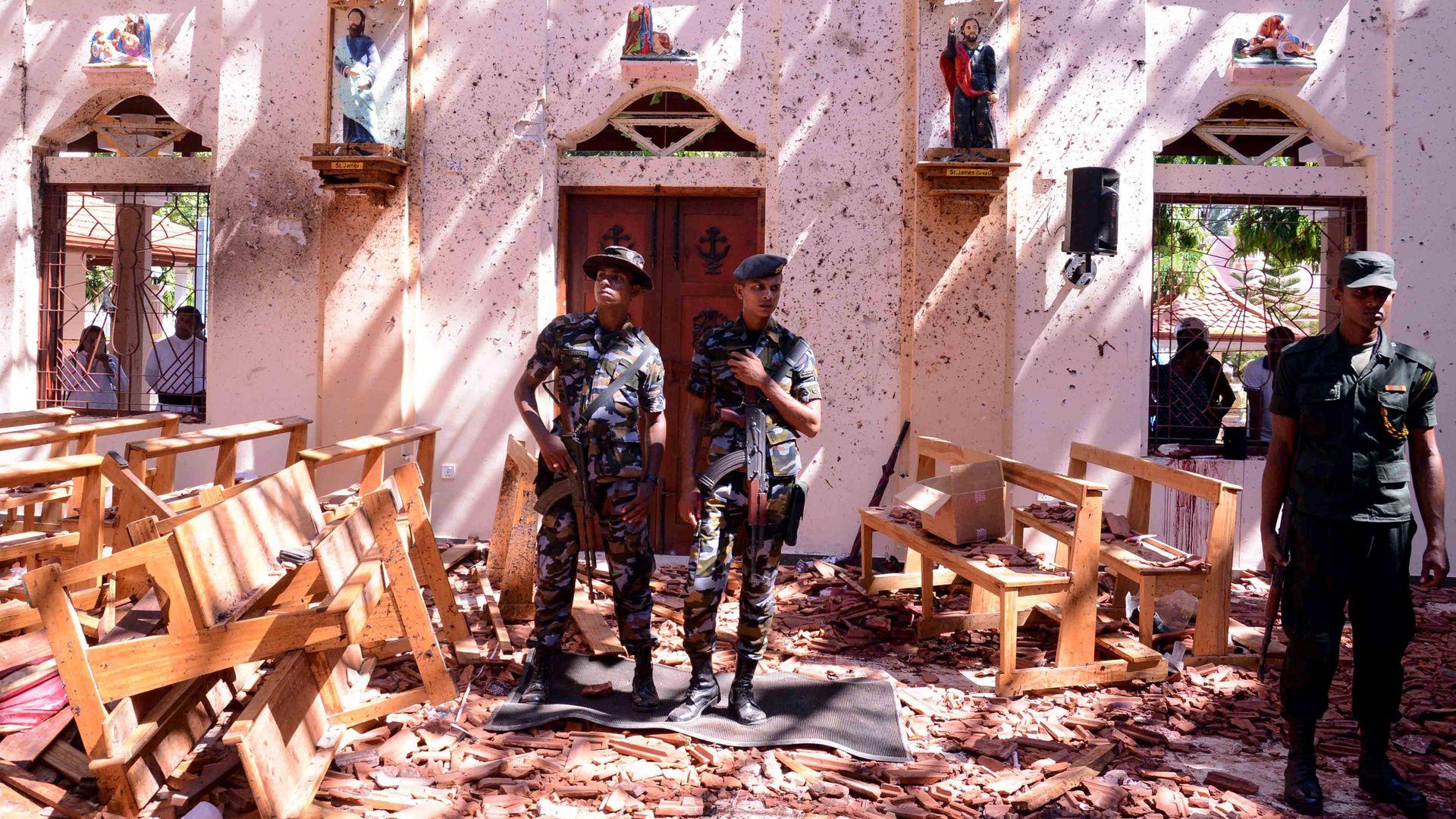 Sri Lankan soldiers look on inside the St Sebastian's Church at Katuwapitiya in Negombo on Sunday.