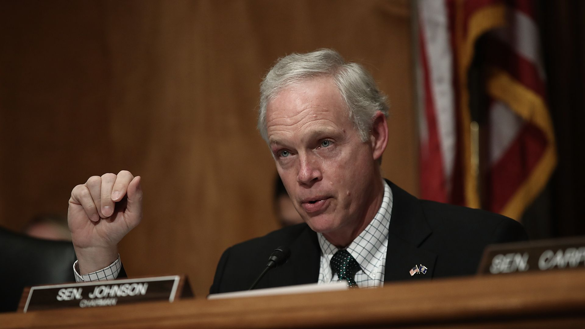 Senator Ron Johnson sits in front of his nameplate on a dais.
