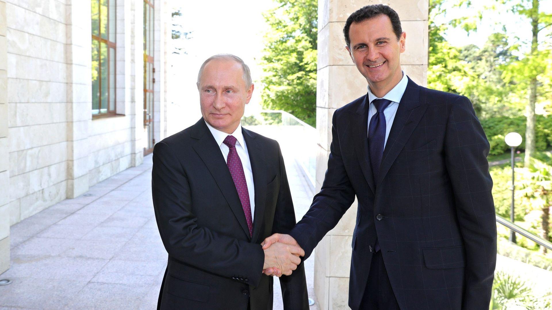 Vladimir Putin and Bashar al-Assad shaking hands and smiling
