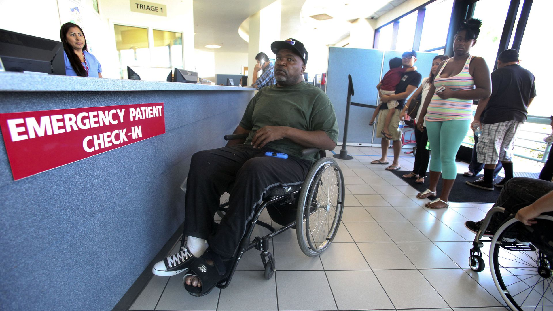 A man in a wheelchair checks in a hospital emergency room.