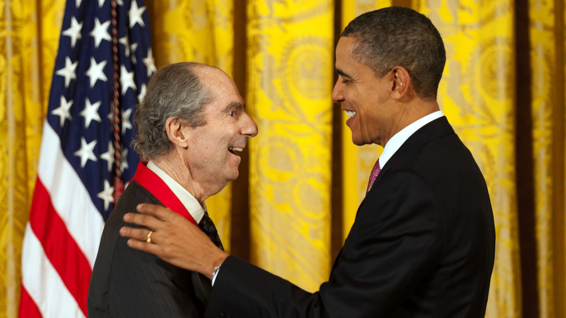 Obama places his hands on Roth's shoulders
