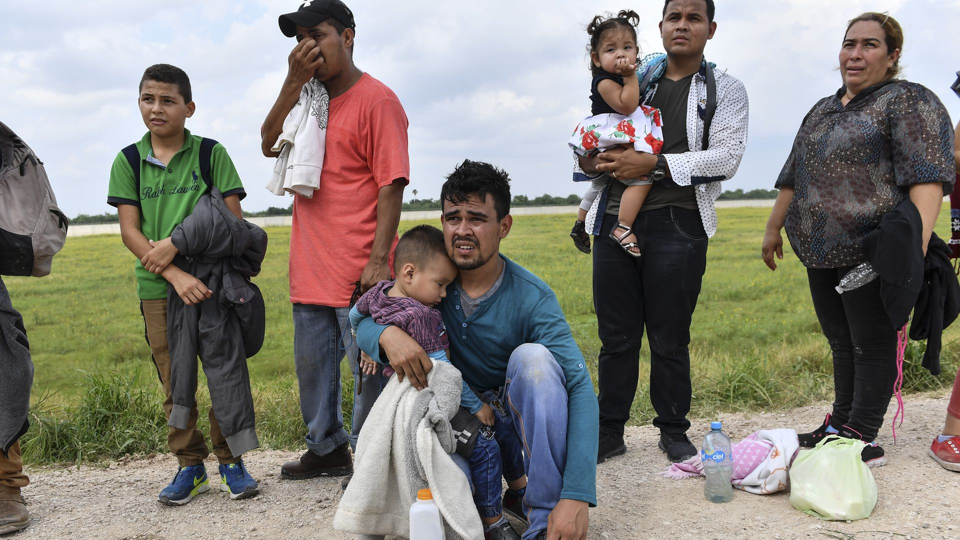 In this image, a line of migrants stand outside, several holding small children.
