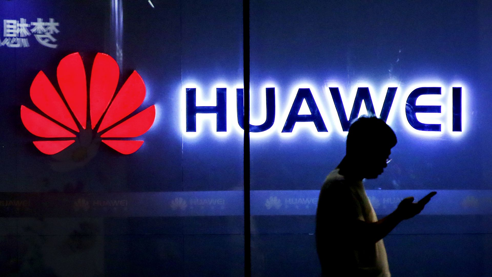Photo of man using a smartphone silhouetted against a glowing Huawei logo