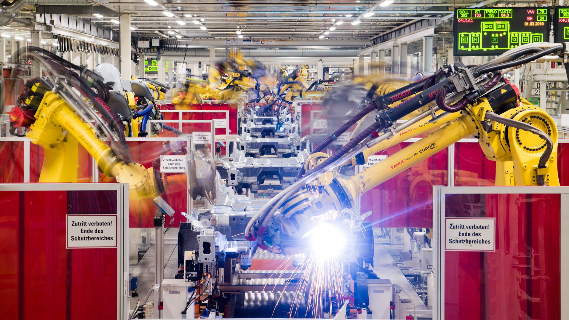 Photo of industrial robots working on cars on an assembly line